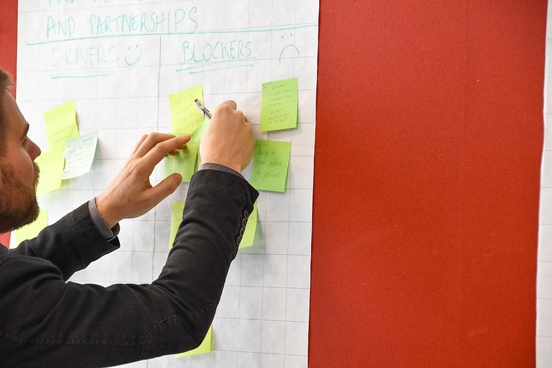 A man placing post-it notes on wall